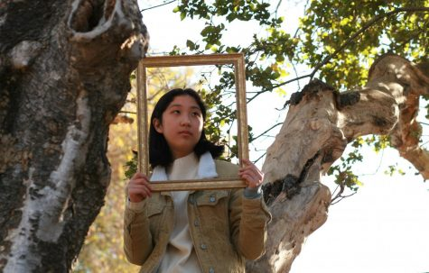"""Opinions editor Nicole Tian (11) holds a frame in front of her face, a self-portrait for her column in the newest """"I Believe"""" repeater."""