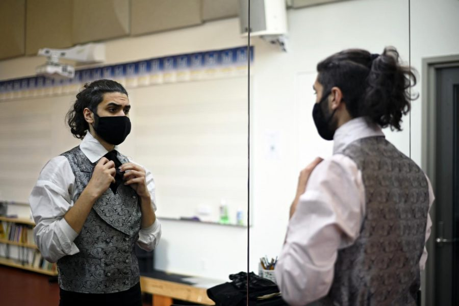 Alex Kumar (12) faces the mirrors in the dressing room as he adjusts his costume. Alex plays the role of protagonist Jean Valjean.