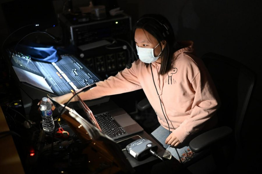 Ysabel Chen (11), one of the assistant directors of the student tech crew, sits in the tech control booth in the audience as she watches the student performers rehearse.