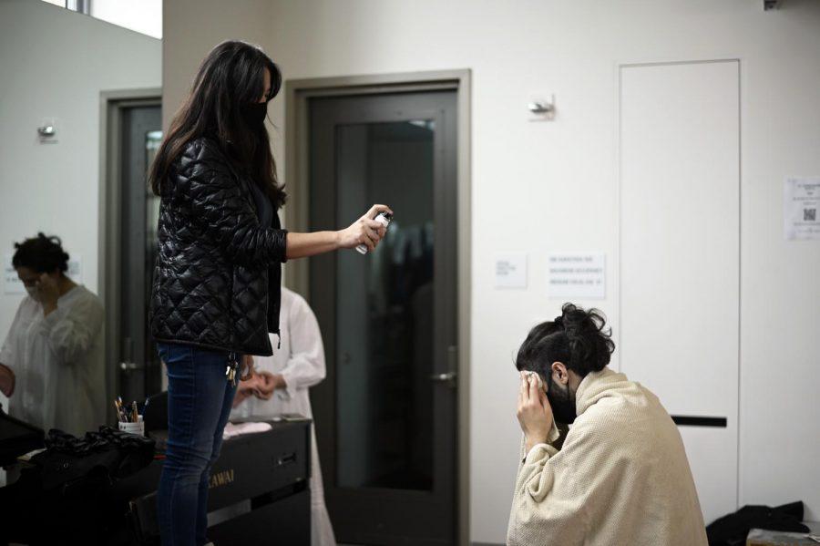 Fuiji sprays hairspray on Alex Kumar (12) in the dressing room before the final few scenes.