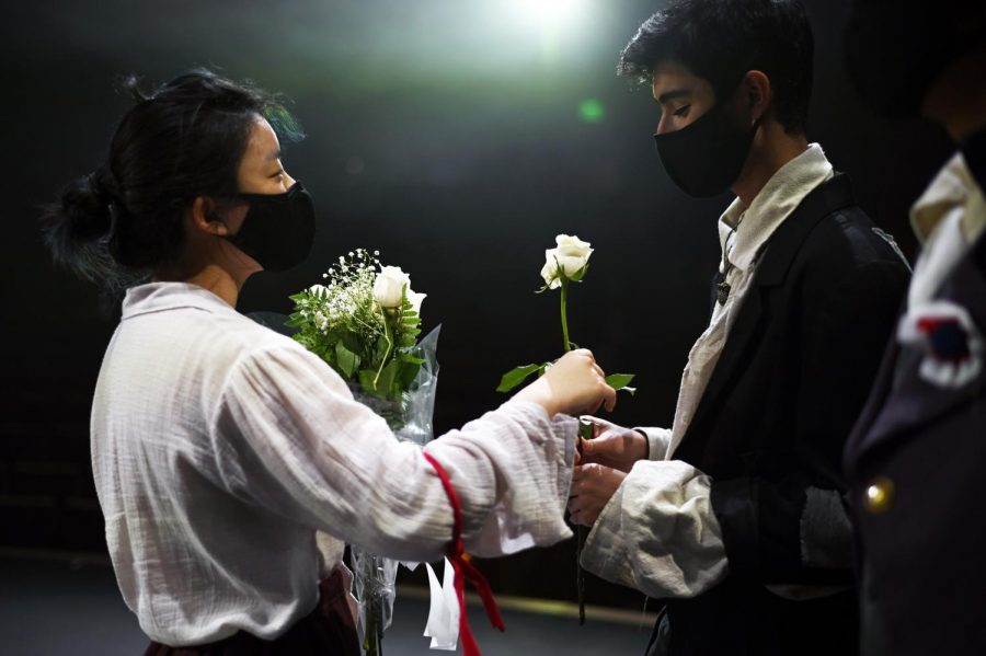 Senior Topaz Gao hands sophomore Zubin Khera one of the flowers in their bouquet as the cast celebrated onstage after finishing the last rehearsal.