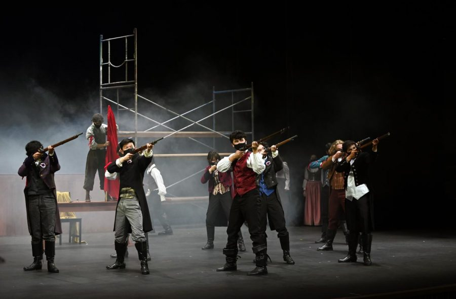 Cast members hold prop muskets on stage during rehearsal. Special effects were added to enhance the play setting, making the revolutionary setting as realistic as possible.