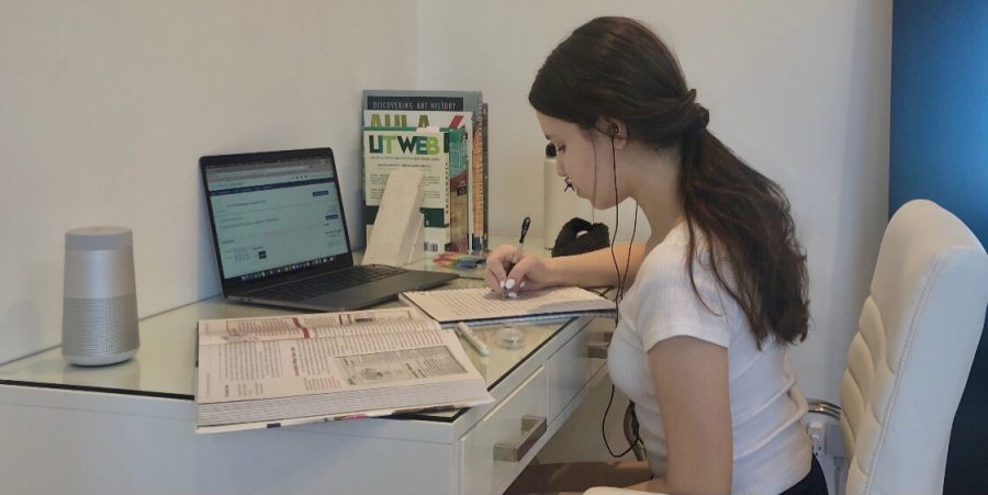 Ariana Goetting (9) works at her desk during remote learning. Upper school students will be taking most of their AP exams from home through a computer.