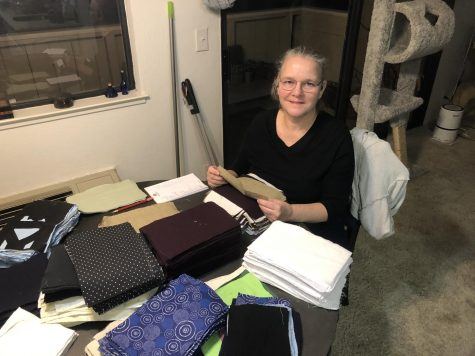 """Library director Lauri Vaughan stacks rectangles of cotton into what she calls """"mask pancakes"""" before sewing them into individual masks. With aid from student volunteers and fabric donors, her sewing project reached 5000 masks, which she announced on Mar. 3 on Schoology."""