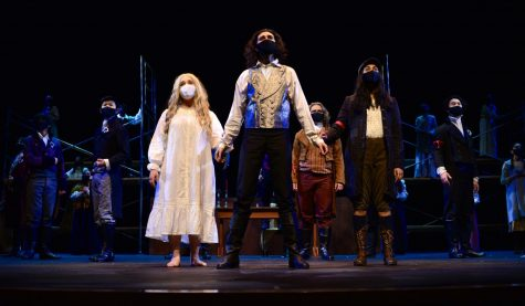 "Seniors Ruya Ozveren, Alex Kumar, and Vaishnavi Murari sing in the closing scene of the spring musical ""Les Misérables"" with the entire cast on March 19. Unlike the format of the Fall Play and Student Directed Showcase (SDS), Performing Arts Director Laura Lang-Ree converted the musical into a movie, where multiple video angles are used and the audio is recorded beforehand."