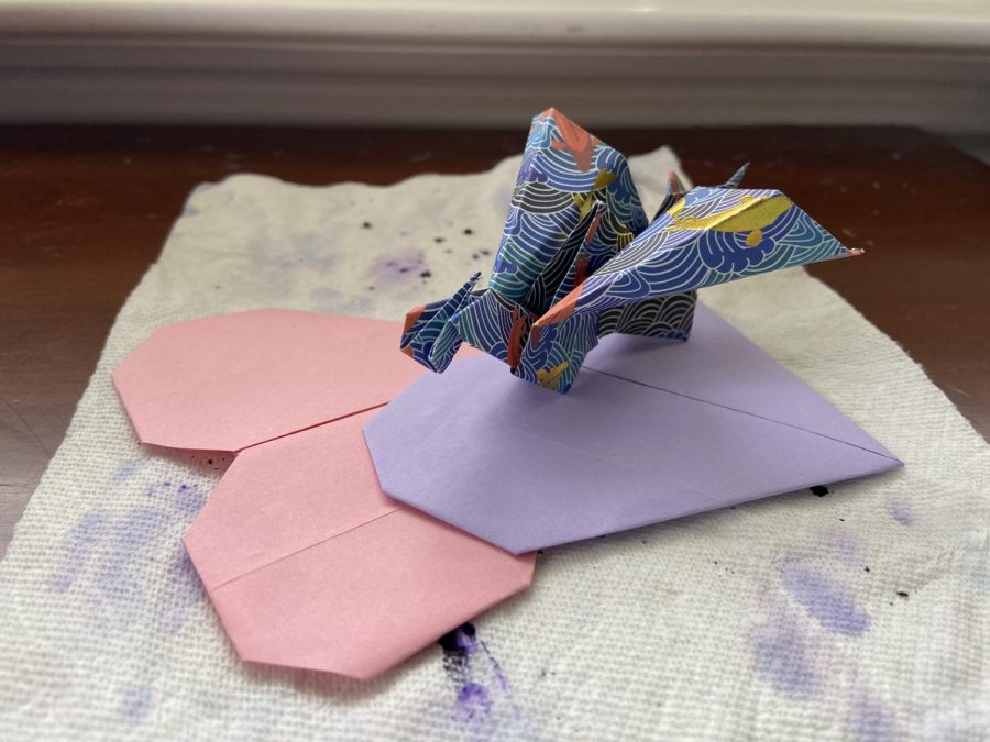 I've had more time to work on arts and crafts during the pandemic, and this origami flapping dragon lying on top of a paper towel with watercolor stains was one of my foldable creations. Following crafting tutorials have given me space to take a breath and litter my desk with small creations.