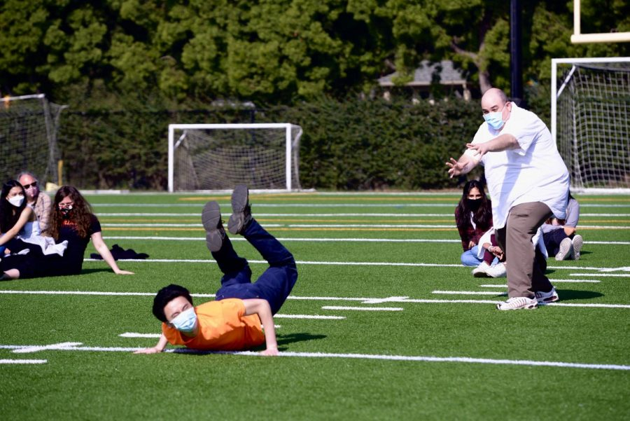 Michael Eng (12) falls to the ground while acting out a yoga pose with his advisor and upper school speech and debate teacher, Scott Odekirk, during a spirit activity on April 19.