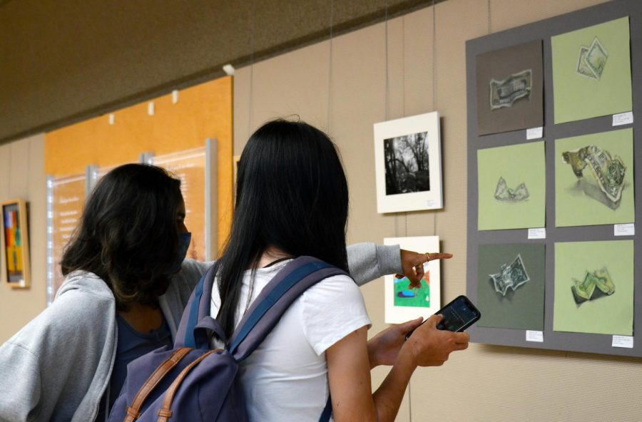 Vidya Jeyendran (12) points at a piece of artwork to Fonda Hu (12) as they walk through the Nichols Atrium. All the exhibitions belonging to the End of Year Art Show are being exhibited across campus from May 7 to May 28.