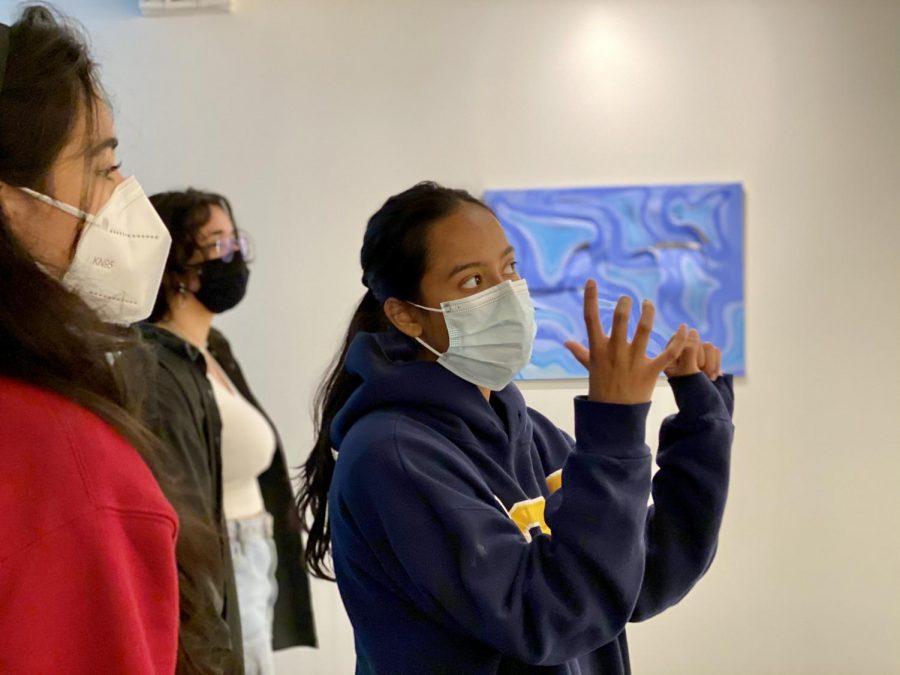 Lisa Barooah (12) discusses Ashley Gauba's (12) art exhibition to Farah Hosseini (12) as Arohee Bhoja (12) views the pieces.