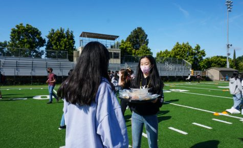 Freshmen class council officer Ella Lan (9) offers individually packaged donuts to a student on April 22 during the morning class spirit activity.