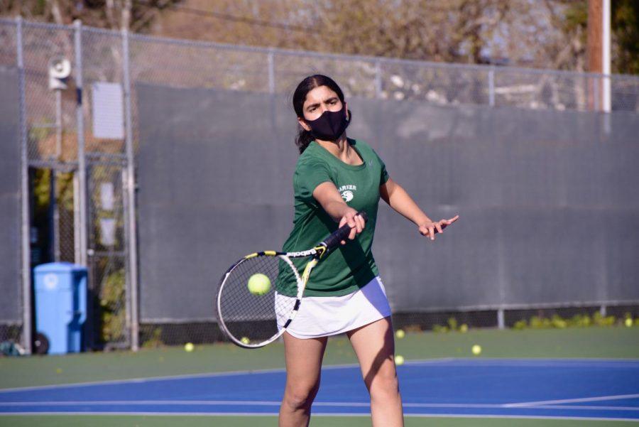 Team captain Sachi Bajaj (12) swings during her doubles match against Castilleja on March 23.