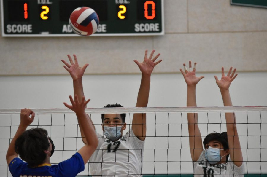 Brian Pinkston (12) and Edis Mesic (9) block an opponent's swing during the second set.