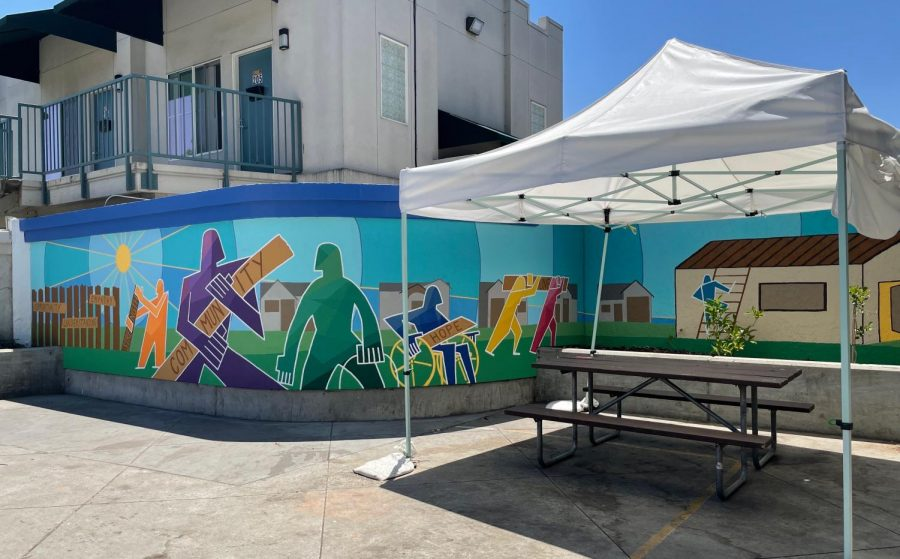 The HomeFirst mural, finished June 19, depicts figures deconstructing a fence to build houses for the community. Led by the Honors Directed Portfolio class, the mural spans 6 feet by 40 feet.