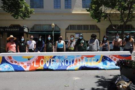 """Art Club members stand behind their work after the completion of the """"Love Not Hate"""" mural in Downtown Palo Alto on June 12. Club members painted the mural in support of the Stop AAPI movement and to show solidarity with the AAPI community."""