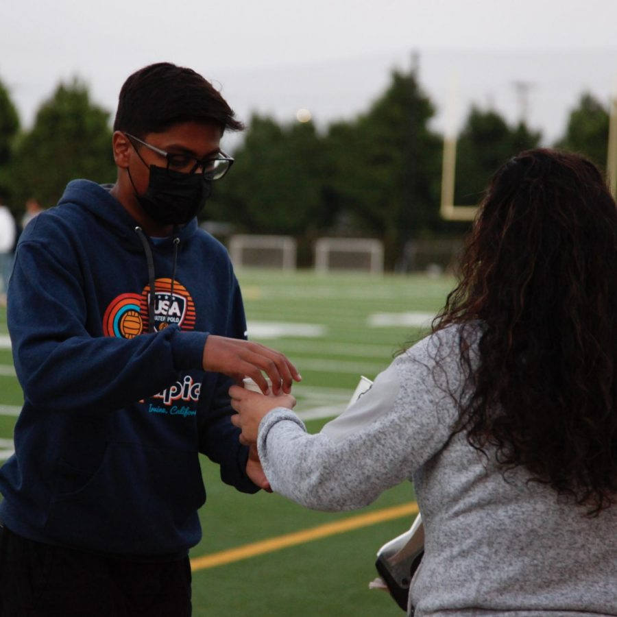 Anish Pai (12) receives a cup of hot chocolate from Director of Alumni Relations Kristina Alaniz. The hot chocolate station included toppings such as caramel sauce, mini marshmallows and whipped cream.