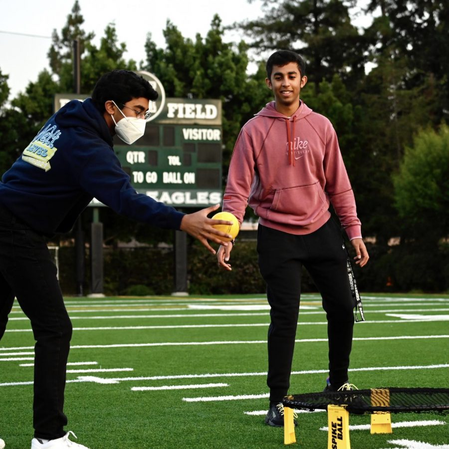 Sasvath Ramachandran (12) and Aaditya Gulati (12) play a game of Spikeball together before school. After the sunrise, some seniors stayed on the field to play games.