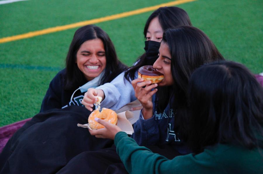 Megha Salvi (12) bites into a chocolate frosted doughnut. The senior class council and senior class dean Christopher Hurshman distributed doughnuts to the seniors.