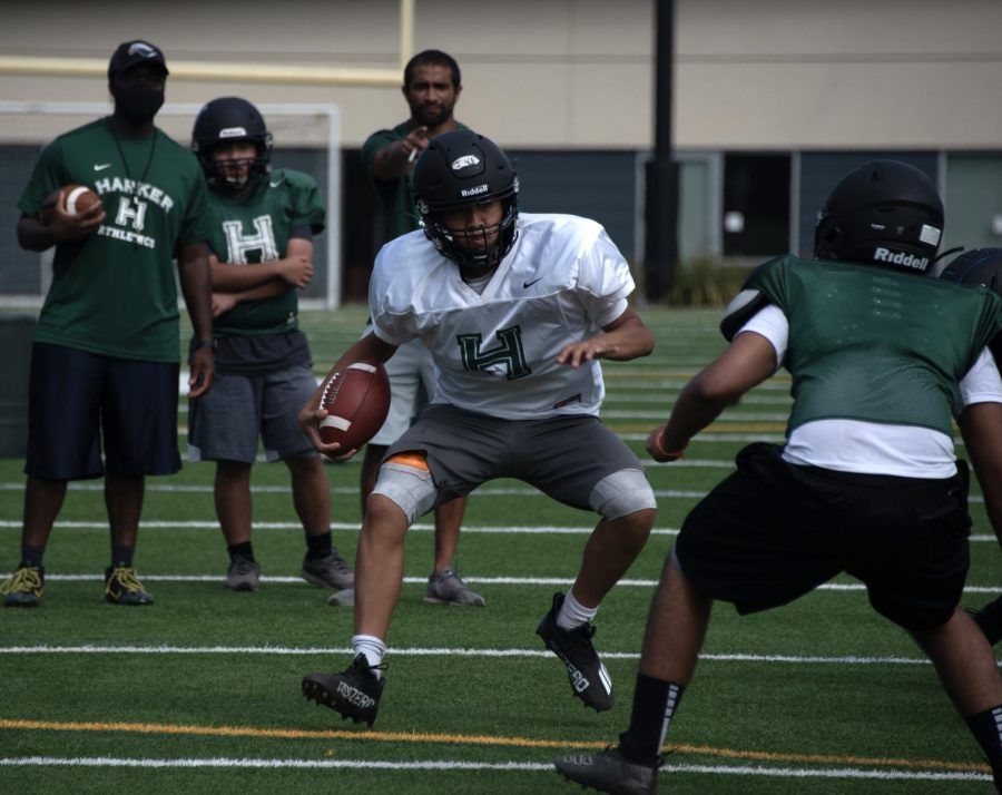 Jason Yi (9) jukes out a defender during football practice on August 13. The football team placed second in a 7 vs. 7 passing tournament in July.