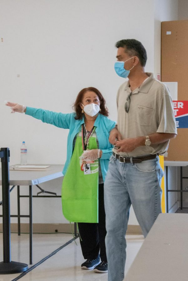 A volunteer guides a voter to the ballot boxes yesterday at the St. Francis of Assisi Parish polling center in San Jose. All active registered voters were mailed a vote-by-mail ballot before the election, but also had the ability to vote in person.