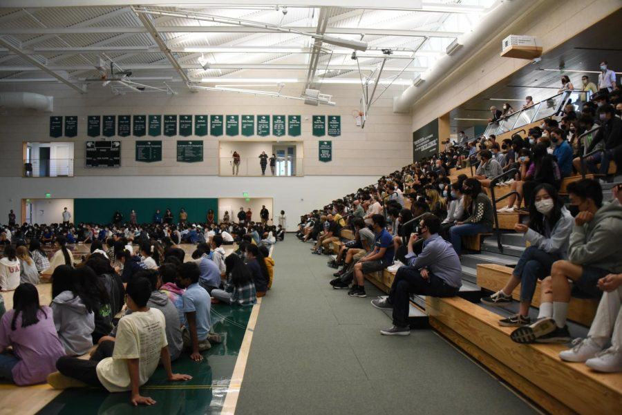 Seniors, juniors and faculty sit on the gym bleachers while freshmen and sophomores sit on the Zhang Gymnasium floor during school meeting. The seating chart, which was displayed at the beginning of the meeting, arranges junior and senior advisories by row.