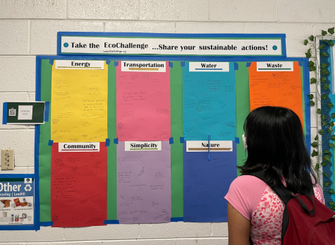 Emma Biswas (11) reads written responses from Green Teams EcoChallenge bulletin board. Honor Week launched today with a focus on the environment and will continue with different daily themes throughout the rest of the week.