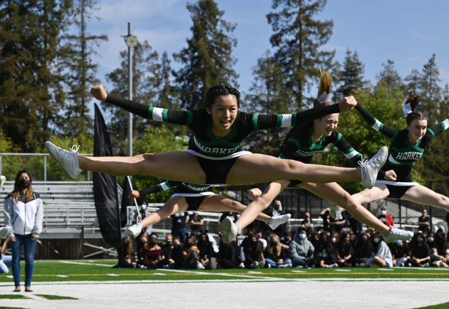 Alex Fu (10), Imogen Lenehem (12) and Sarah Westgate (10) jump into splits in the air. The three are part of Harkers varsity cheerleading team and performed the rally.