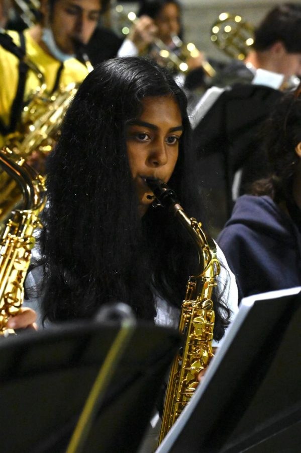 Isha Kotalwar (10) plays the saxophone. Jazz Band played a variety of songs, including a rendition of Skyfall after the game ended.