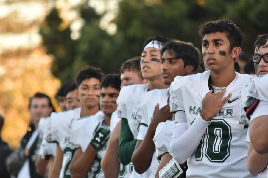 Aaditya Gulati (12) puts his hand on his heart while the all-school choir sings The Star Spangled Banner. The game began after the anthem with kickoff from Marina.