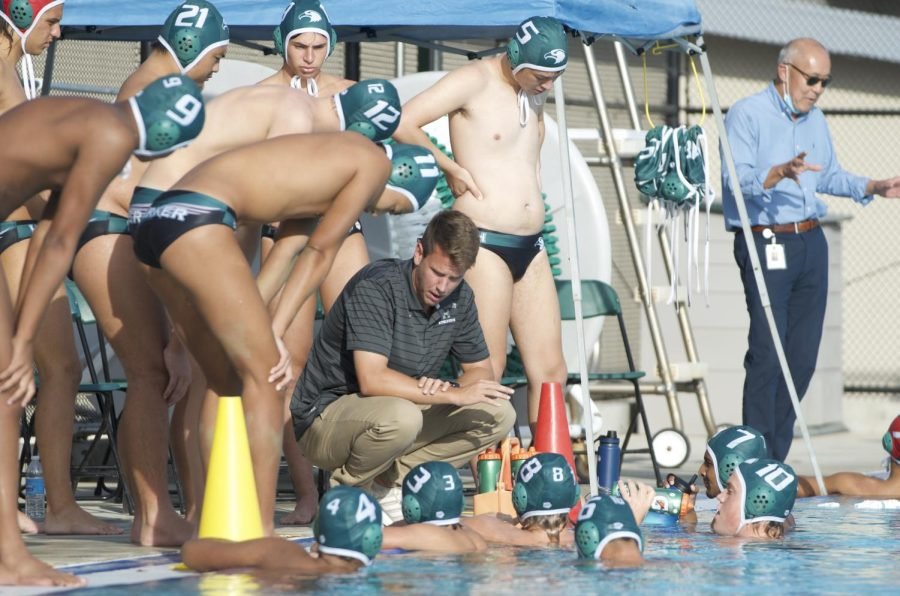 The varsity boys water polo team huddles up during a timeout in the second quarter.