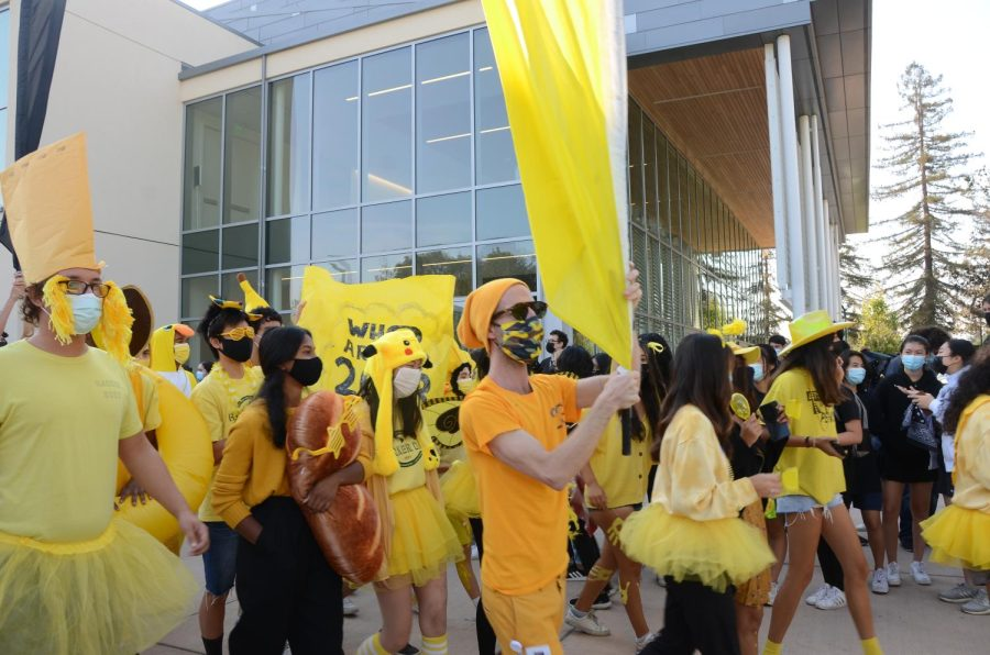 The junior class advisory representatives, led by class dean Karl Kuehn waving a yellow flag, marches in the parade during the spirit rally, decked in their class color, yellow. Each class embellished their outfits to show class pride during the rally by wearing their according class colors: white, black, yellow and green for freshmen, sophomores, juniors and seniors, respectively.