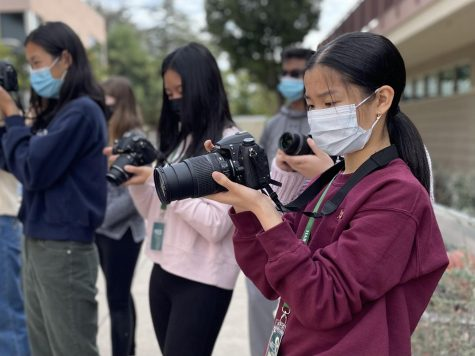 Reporter Ella Yee (10) reviews photos taken of a table tennis match between Director of Journalism Ellen Austin and Winged Post Managing Editor Mark Hu (12). All periods of news-based journalism students engaged in action photography practice today.