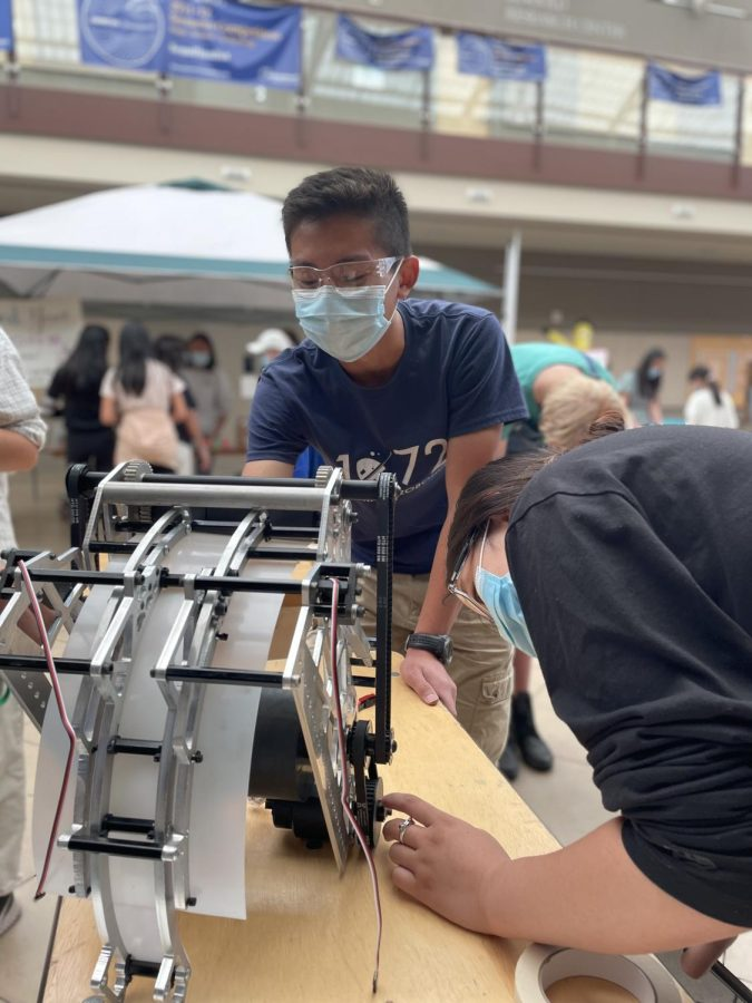 Harker Robotics members Alex Liou (12) and Gloria Zhu (12) examine the shooter portion of the teams robot. The robotics team hosted an activity in Nichols Hall where Harker Day attendees could try their hand at driving the robot.