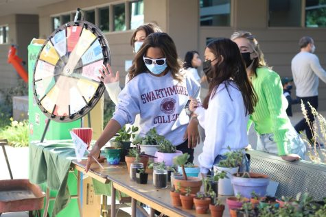 Medini Halepete (10) adjusts the Green Team booth, which featured a spin-the-wheel with environmental questions and potted succulents in front of Nichols Hall. Fourteen different upper school clubs hosted booths in or in front of Nichols and in the quad, with posters and interactive games or activities, many designed for lower or middle school students.