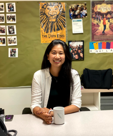 Upper school Intro to Journalism teacher Whitney Huang sits at her desk in the back room of the journalism classroom, holding her Harker Journalism mug. Huang, a 2008 alumna and Harker lifer, returned to Harker due to her deep connection to the schools culture and environment.