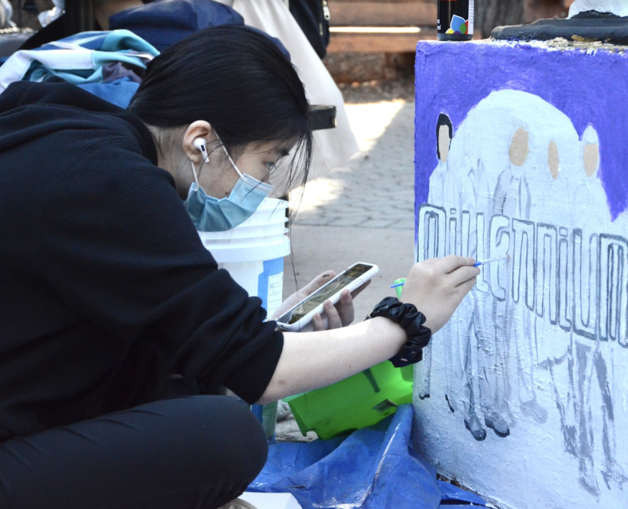 Angelina Hu (10) paints the Backstreet Boys album Millenium on the side of the sophomores class eagle.