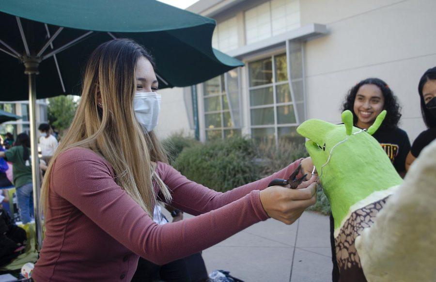Senior Student Activities Board (SAB) representative Kate Olsen fastens a headband with Shrek ears made of polymer clay onto the senior eagle.