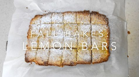 A freshly baked batch of lemon bars sits in a tray with parchment paper. Follow along with this lemon bar recipe that is perfect for the fall.